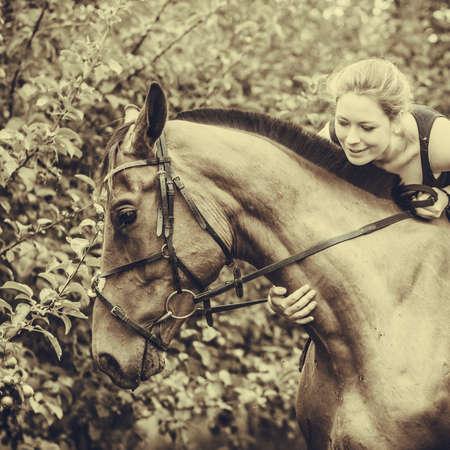 Young woman animal lover hugging horse outdoor, garden background, sepia, vintage tone