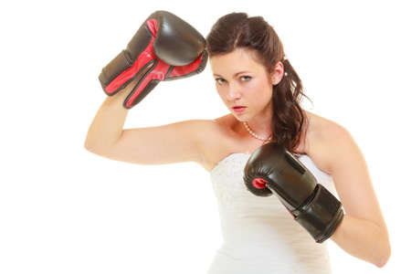 Violence in relationship concept. Dominant bride wearing wedding dress and boxing gloves photo