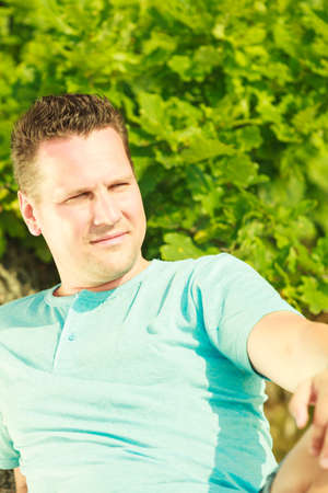 Outdoor nature relaxation concept. Handsome man spending his free time outside during summertime photo
