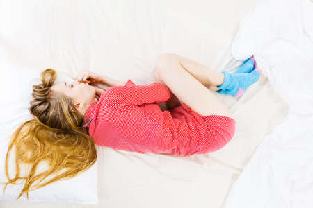 Teenage sleepwear fashion concept. Young woman lying on bed wearing cute pink pajamas. Top view Imagens