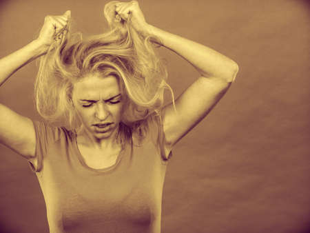 Haircare, health problem concept. Frustrated, depressed woman holding and pulling out her damaged blonde hair with closed eyes. Sepia