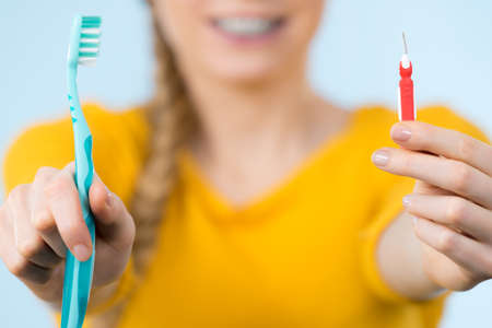 orthodontist: Dentist and orthodontist concept. Young woman smiling cleaning and brushing teeth with braces using toothbrush Stock Photo
