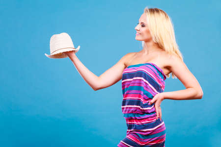 Summer trendy fashionable outfit ideas concept. Blonde woman wearing short colorful striped strapless dress holding white sun hat Stock Photo