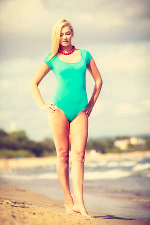 woman bath: Being trendy and fashionable during summer vacation concept. Blonde slim attractive woman walking on beach wearing blue one piece swimsuit.