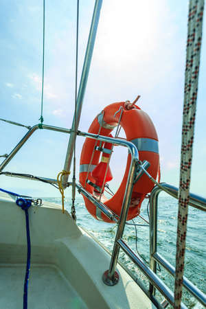 Rescue red lifebuoy life preserver saver ring on sailboat. Yachting in summer time