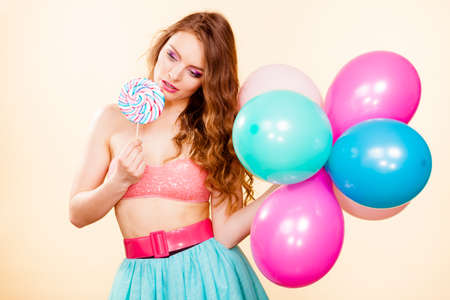 Woman smiling cheerful girl holding colorful balloons and sweet lollipop in hands. Summer holidays, celebration and happiness concept. Studio shot bright