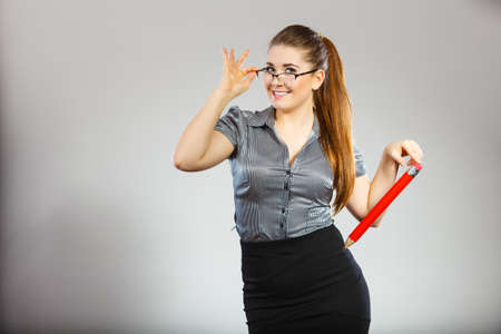 Teacher looking elegant woman wearing dark tight skirt, shirt and eyeglasses holding big oversized pencil