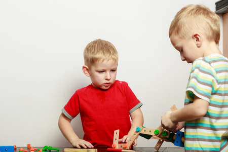 Childhood, kids imagination concept. Concentrated two little boys playing with toys having fun