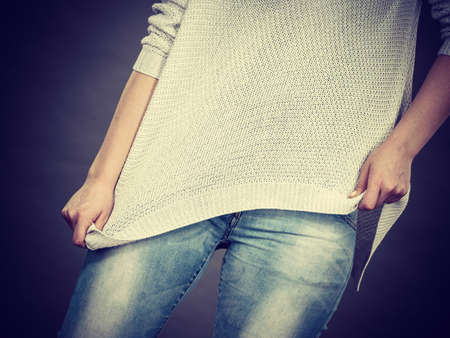 Unrecognizable woman wearing too big jumper, not fitting after weight loss. Grey background