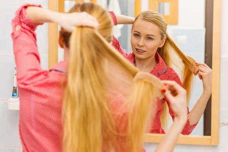 Woman combing brushing her long smooth hair in bathroom, looking in mirror. Girl taking care refreshing her hairstyle. Haircare concept. Stock Photo
