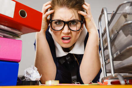 mobbing: Mobbing at work, bad job relations concept. Depressed businesswoman being sad and tired sitting working at desk full off documents in binders.