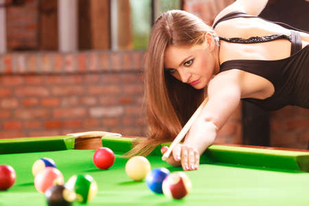 Competition concept. Young focused girl having fun with billiard. Pretty fashionable woman spending time on playing rivalry. Banque d'images