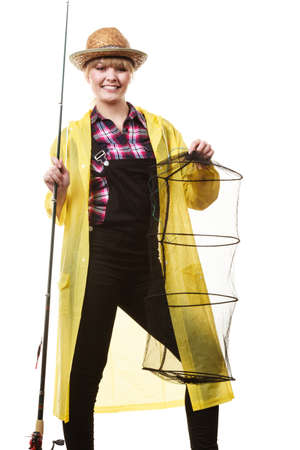 dungarees: Spinning, angling, cheerful fisherwoman concept. Happy woman in yellow raincoat holding fishing rod and keepnet having fun. Stock Photo