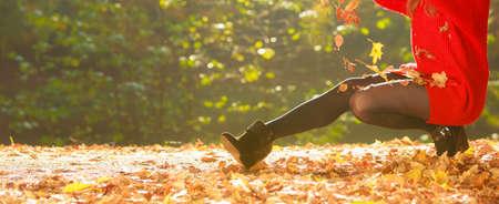 Herfst tijd. Plezier en zorgeloos. Vrolijke mooie jonge vrouw spelen met bladeren. Meisje ontspannen in de herfst park bos, omgeven door bomen met vliegende blad. Stockfoto