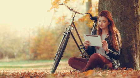 Technology internet modern lifestyle concept. Woman in autumn park using tablet computer reading. Girl with e-book reader touchpad pc outdoor