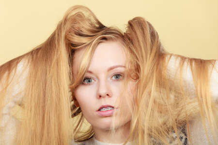 Haircare, hairstyling, bleaching concept. Blonde woman holding her long tangled hair, closeup.