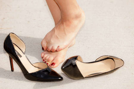 Hurting feet problem. Woman standing barefoot, high heels lying against her, having enough of pain.