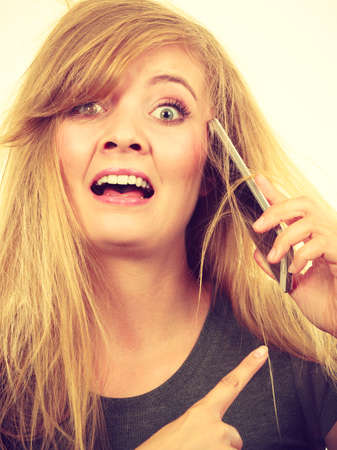 Unpleasant conversation, bad relationships concept. Crazy young blonde weirdo woman with messy hair talking on phone Stock Photo