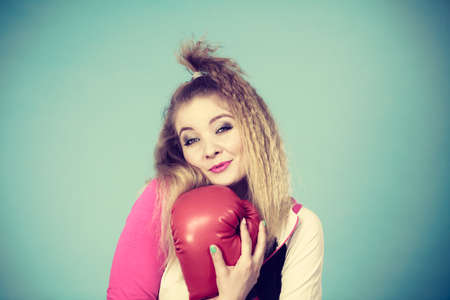 Funny cute blonde girl female boxer with big fun red gloves playing sports boxing studio shot on blue