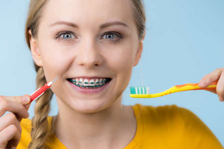 Dentist and orthodontist concept. Young woman smiling cleaning and brushing teeth with braces using toothbrush Stock Photo