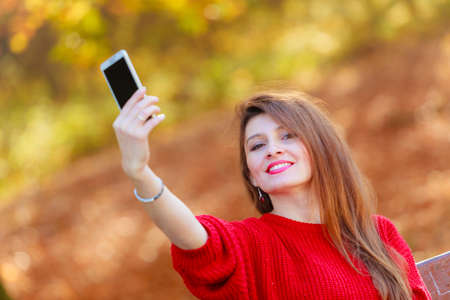 Technology and fun concept. Enjoyable attractive girl playing with mobilephone. Cheerful gorgeous woman smiling taking selfie photo in seasonal autumnal park forest. Stock Photo