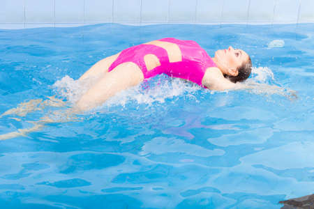 Beautiful young woman in pink swimsuit swimming in blue pool on her back. Young female swimmer at holiday resort. Sport activity health concept.