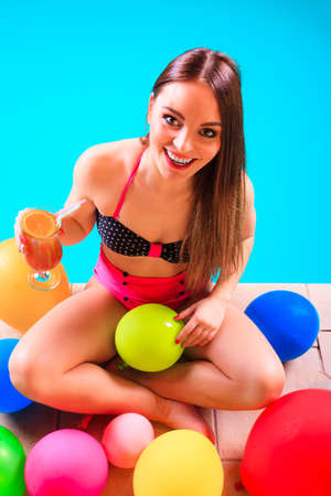 Happy woman having fun with balloons and cocktail drink alcohol. Pretty attractive girl relaxing at swimming pool edge poolside. Stock Photo