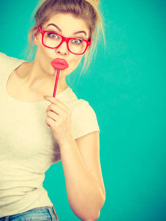 Lovely sweet woman casual style nerdy glasses holding red fake lips on stick having fun, on green blue. Photo take and carnival funny accessories concept.