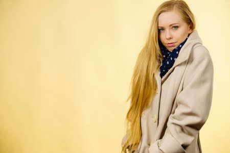 Mulher que veste o frio bege outonal do sentimento do revestimento. Sobretudos de outono, conceito de roupa e moda. Studio atirou em fundo amarelo