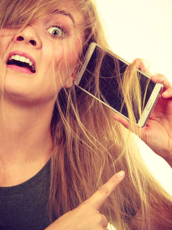 uncouth: Unpleasant conversation, bad relationships concept. Crazy young blonde weirdo woman with messy hair talking on phone Stock Photo