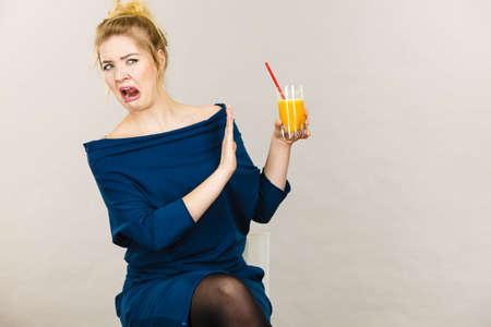 Disgusted blonde woman holding orange juice, lady not enjoying fresh fruit drink.