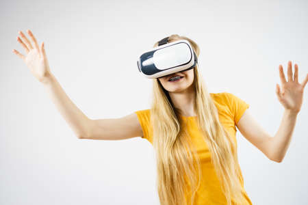 Young woman wearing virtual reality goggles headset, vr box, stretching arms. Studio shot on gray. Concept of connection, technology, new generation and progress.