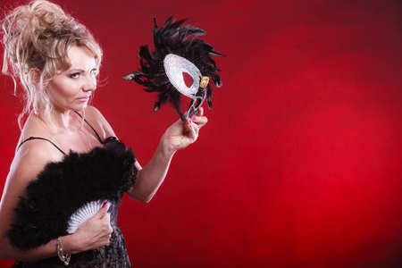 Holidays, people and celebration concept. Woman blonde middle aged model holding in hand black carnival mask, feather fan on festive color background Stock Photo