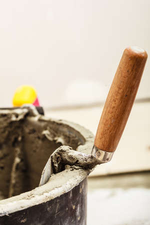 Housework renovation tools concept. Trowel, tool for cement scooping in basket with mortar Stock Photo