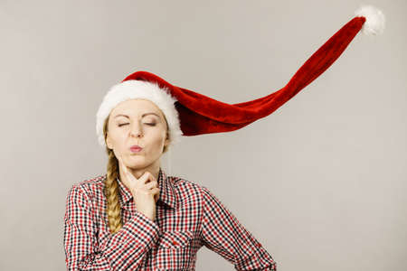 silly face: Young woman funny teen girl closed eyes wearing blowing santa claus hat thinking. Christmas time. Studio shot on grey Stock Photo