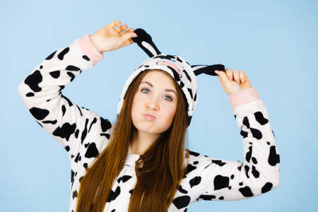 People dressed up like animals concept. Happy teenage girl in funny nightclothes cow pajamas costume, pyjamas cartoon style, smiling positive face expression, studio shot on blue. Reklamní fotografie