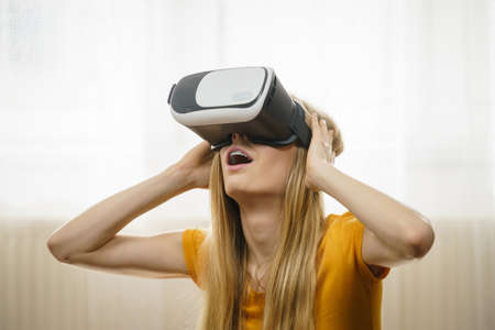 Young woman wearing virtual reality goggles headset, vr box. Indoot at home. Connection, technology, new generation and progress concept.