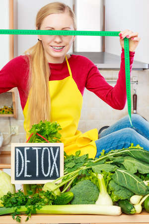 medula: Young woman in kitchen having many green vegetables presenting board with detox sign.
