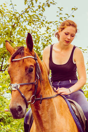 Animal, horsemanship concept. Young woman sitting and ridding on a horse through garden on sunny spring day Stock Photo