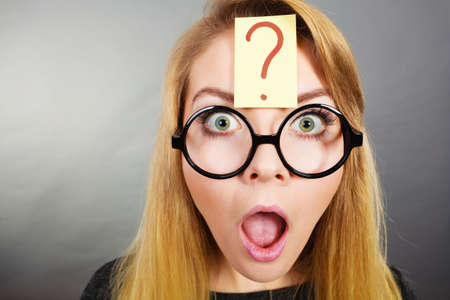stupidity: Crazy wondering face expression concept. Wierdo nerd woman having question mark on forehead and geek eyeglasses. Stock Photo