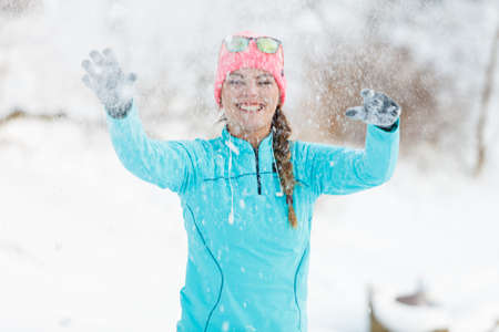 Girl playing with snowball. Relax entertainment with winter nature. Health fitness fashion concept.