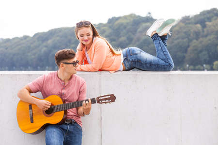 Love romance sound talent passion concept. Charmed girl enjoying music. Young lady listening to man playing guitar.