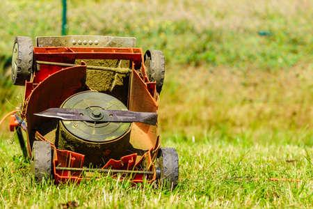 Tuinieren. Gebroken oude grasmaaier in achtertuin gras. Stockfoto