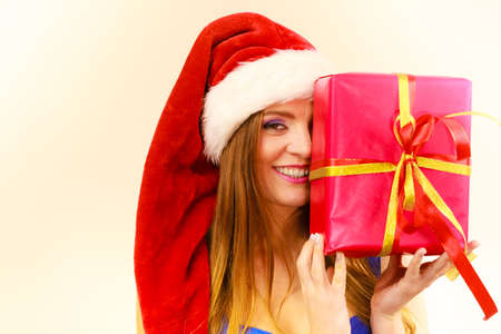 Lovely woman wearing santa claus hat holding big red christmas present, hiding her face behind gift. Xmas, happiness, winter and people concept Stock Photo