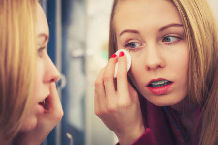 woman mirror: Skin complexion care concept. Young woman using cotton pad to remove make up or dirt from face. Stock Photo