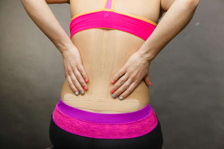 back ache: Woman with kinesiotaping application for back pain. Backache alternative kinesio tape therapy method. Health and body care. Stock Photo