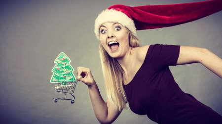 Kerstmis, seizoensgebonden verkoop, winterfeestconcept. Gelukkige vrouw draagt kerstman helper hoed met boodschappenmand karretje met kleine kerstboom binnen te koop.