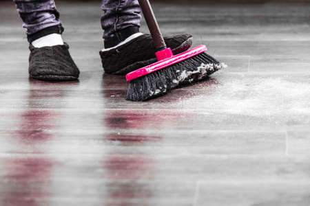 Cleanup housework concept. Closeup broom and female foots. Cleaning woman sweeping wooden floor. Stock Photo