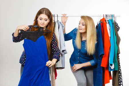 Happy young women during shopping time picking clothes for perfect fashionable outfit.
