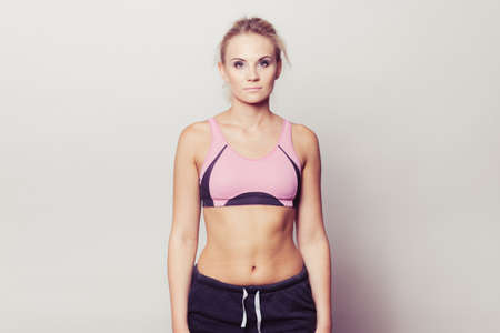 Portrait of sporty fit fitness woman. Attractive girl wearing sporty bra shorts